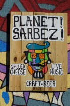 This is just one of the handmade and painted signs that adorn Planet Sarbez, all made or acquired by owner Ryan Kunsch.